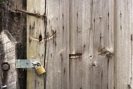 Old weathered shed door and modern unlocked padlock Reklamní fotografie
