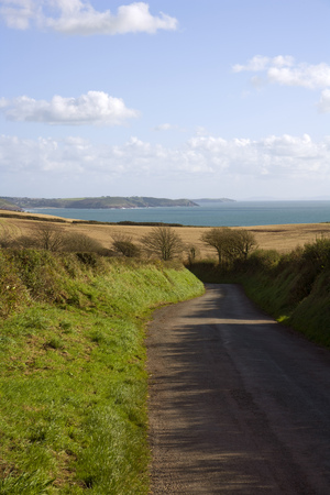 UK, Wales, Pembrokeshire, empty country road winding down towards coast