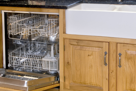 Empty open dishwasher next sink and kitchen cupboards