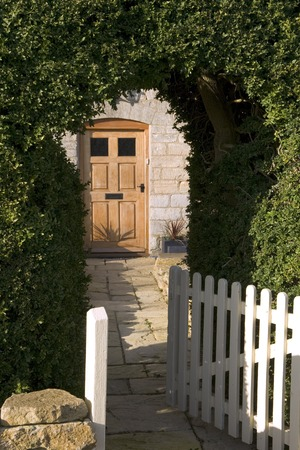 Open garden gate through a hedge and path leading to a front door