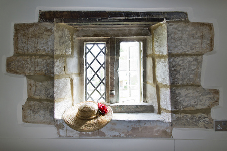 Looking out through an old window. A straw hat is on the window ledge.