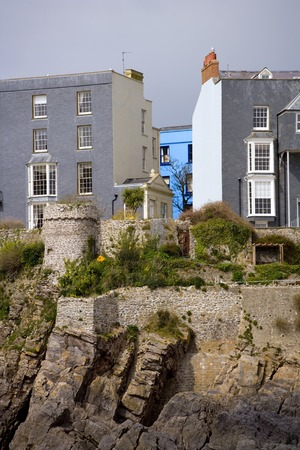 UK, Wales, Pembrokeshire, Tenby, a vibrant blue painted house stands out amongst the grey houses and sky above the cliffs