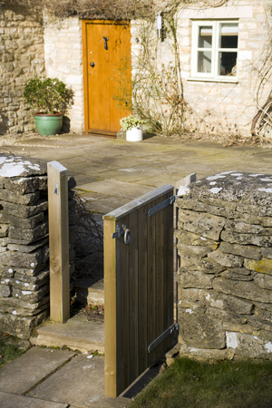 An open garden gate leading to a stone cottage front door