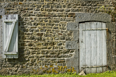 Flaking paint on an old door and shutter set in a neatly pointed restored stone wall