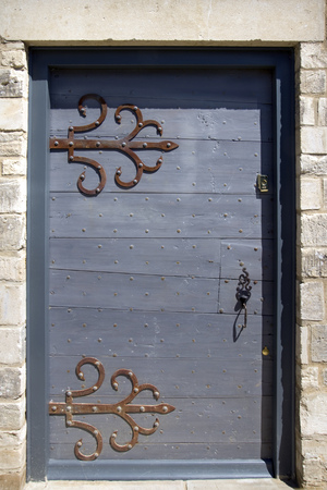 Old painted studded wooden front door with large ornate hinges