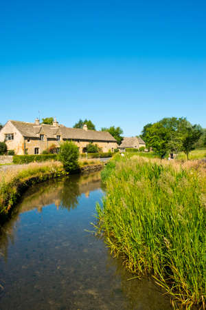 Lower Slaughter, Gloucestershire, UK - 19th July 2016: Summer sunshine brings visitors to the picturesque Cotswold village of Lower Slaughter, Gloucestershire, UK. The village straddles the tiny River Eye and several small footbridges and a ford join the