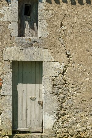 A large crack in the wall of a rustic outbuilding threatens its stability. Banco de Imagens