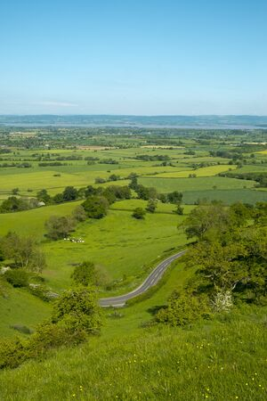 Extensive view towards the River Severn and The Forest of Dean over a patchwork of fields with a winding road in the foreground, Coaley Peak Picnic Site and Viewpoint, Gloucestershire, UK