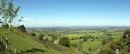 Panoramic view towards the River Severn and The Forest of Dean over a patchwork of fields with a winding road in the foreground, Coaley Peak Picnic Site and Viewpoint, Gloucestershire, UK Reklamní fotografie