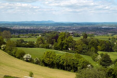 Extensive views over the City of Gloucester in the Severn Vale with the Malvern Hills in the distance. From Cud Hill Common on the western edge of the Cotswolds, Gloucestershire, England, UK