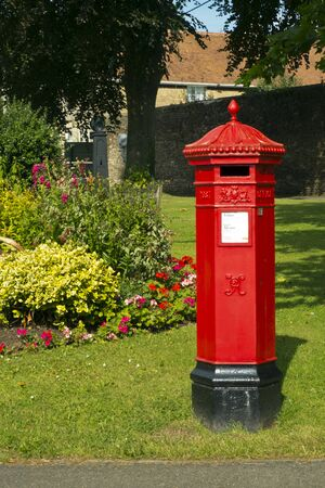 A traditional old red Victorian royal mail post box still in use in the Cotswold town of Tetbury, Gloucestershire, UK