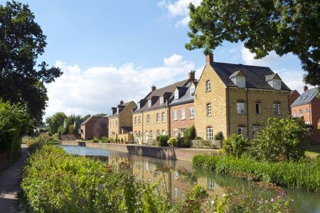 Recently built housing enhances the historic canal near Ebley Mill on the restored Stroudwater Canal, Stroud, Gloucestershire, UK. Фото со стока