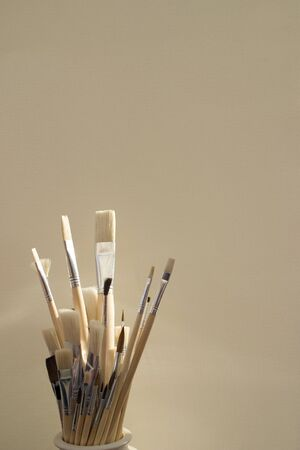 Artists paint brushes in pot in front of a plain background Фото со стока