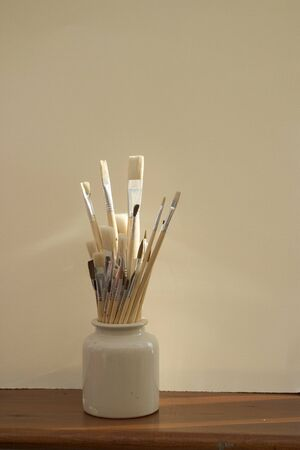 Artists paint brushes in pot on white background Фото со стока