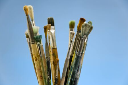 Well used artists paintbrushes on a blue background Фото со стока