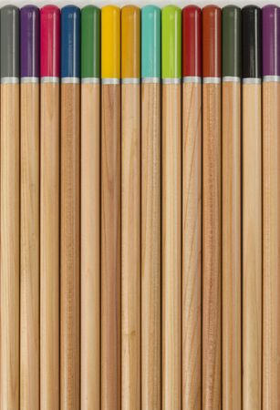 Artists watercolour pencils on a textured white paper surface, the wood and coloured pencil end make a pattern