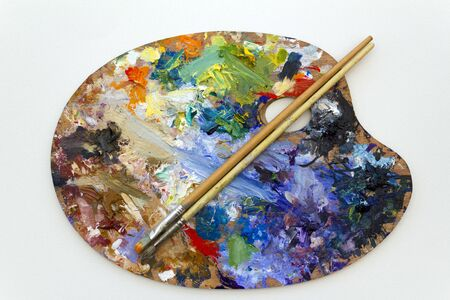 Vibrant multi-coloured artists oil or acrylic paints palette on textured white paper with paintbrushes Фото со стока