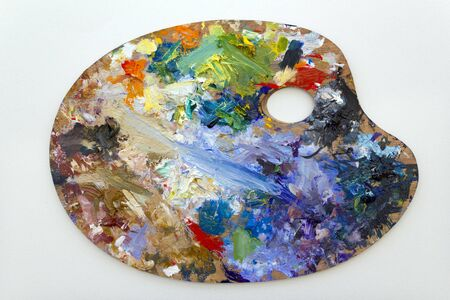 Vibrant multi-coloured artists oil or acrylic paints palette on textured white paper