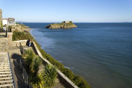 A couple enjoy the view from clifftop gardens in winter sunshine, Tenby, Pembrokeshire, Wales, UK. Tenby experiences a maritime climate with cool summers and mild winters and is one of the sunnier locations in Wales.