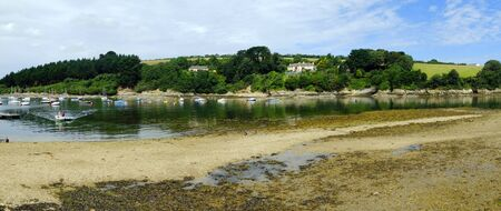 Low tide and a calm summer morning bring a few boats out onto the creek at St Just in Roseland on the picturesque Roseland Peninsula in Cornwall, UK