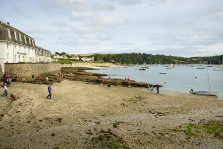 Visitors enjoy the beach at low tide on a summer afternoon in St Mawes on the Roseland Peninsula, Cornwall, UK