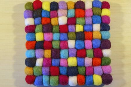 Close up full frame view of a vibrant multi coloured felt booble table mat