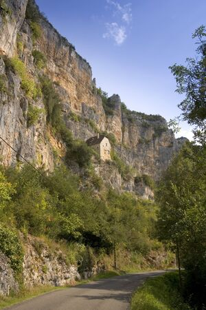 Europe, France, Quercy, Lot, old stone houses built on the side of the cliffs above the River Cele at Sauliac Sur Cele Фото со стока