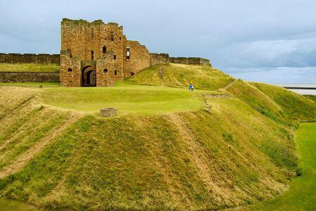 portcullis: Rovine del monastero di Tynemouth con erba riempito fossato
