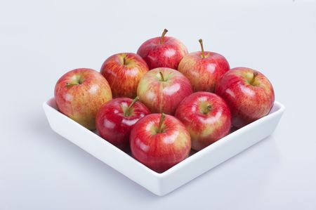 Red Apples in square white bowl over white background photo