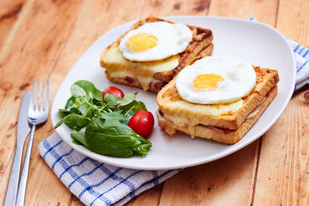 Croque madame with salad on a wooden table