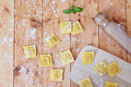 perle: Raw ravioli pasta with flour on wooden table, with kitchen tools