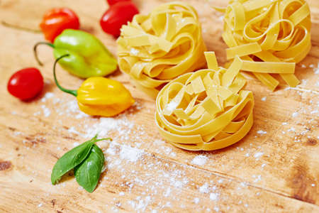 Raw tagliatelle with vegetables on  wooden table photo