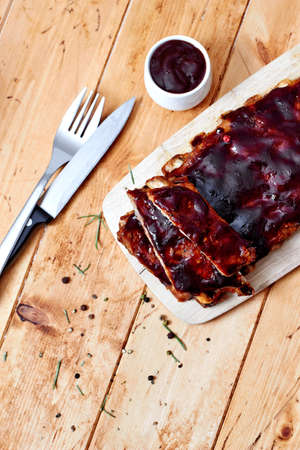 Barbecue ribs with sauce on wooden table, top view