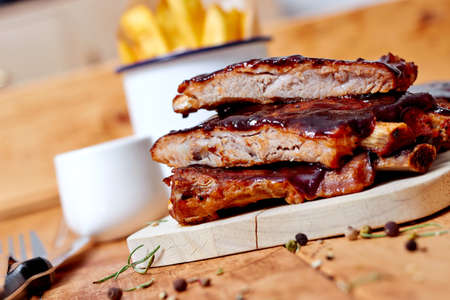 Barbecue ribs with fries on wooden table photo