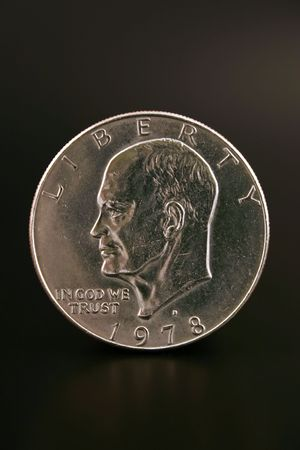 minted: An Eisenhower silver dollar islolated on a black background