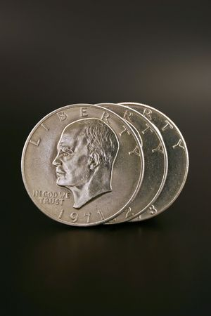 minted: Three Eisenhower silver dollars isolated on a black background