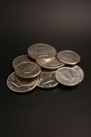 minted: A group of silver dollars and half dollars isolated on a black background