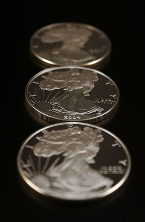 minted: Three American Eagle Silver Bullion Coins (legal tender) shot against a black background Stock Photo