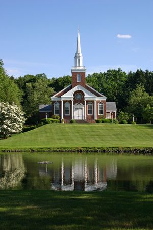 A beautiful church on a hillside overlooking a pond photo