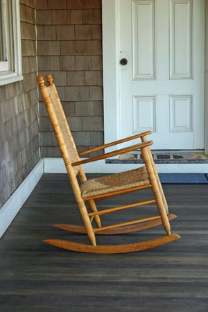 A rocking chair on the porch of a beach house