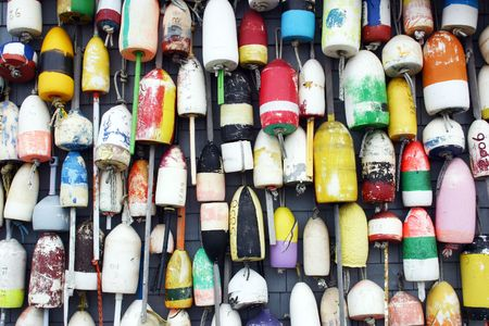 A group of lobster buoys hanging on the side of a building in the harbor of Provincetown, Massachusetts Stock Photo