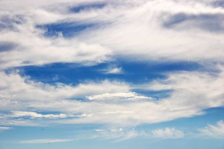 A beautiful blue sky with wispy white clouds photo