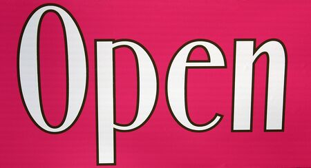 stating: A pink sign stating the business is open