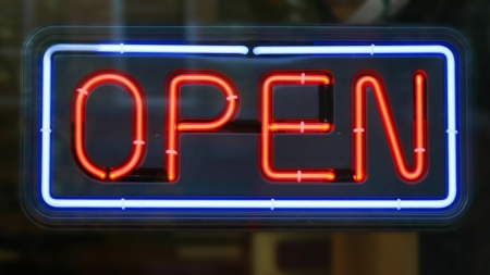 An open sign in the window of a retail establishment photo
