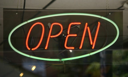A green and orange open sign in the window of a cafe photo