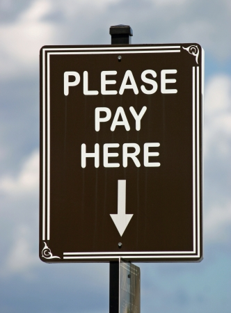 A brown sign reading Please Pay Here against a sunny sky Stock Photo - 14410525