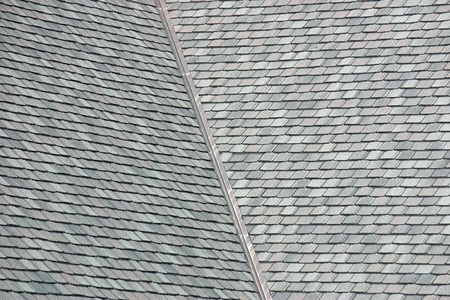 The grey shingles on a large rooftop photo