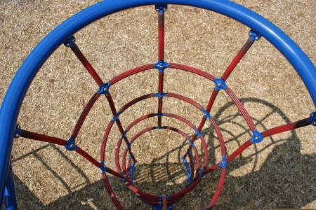 A circular net ladder in an empty playground photo
