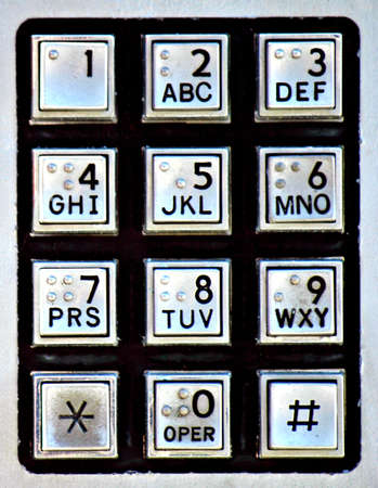 phone button: A silver and black keypad on a public payphone