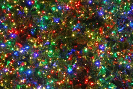 A close up of a Christmas tree with multi colored lights